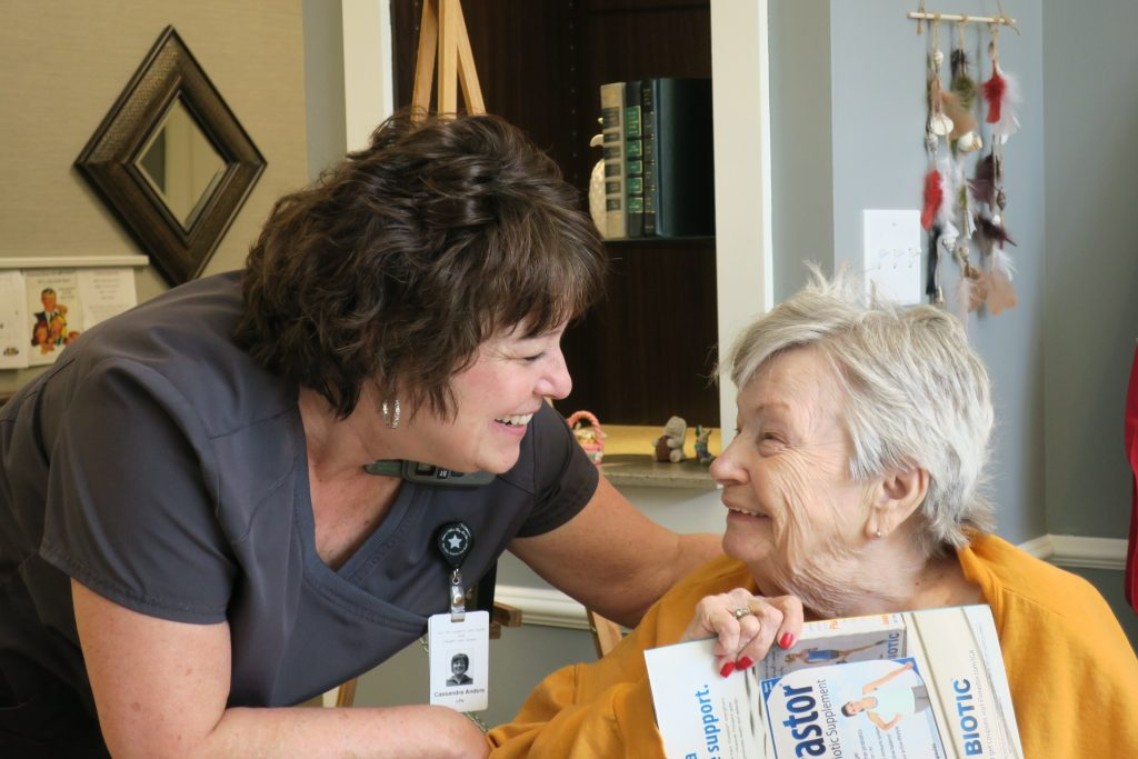 An OESH care partner with a clip-on badge congratulating a smiling elder.