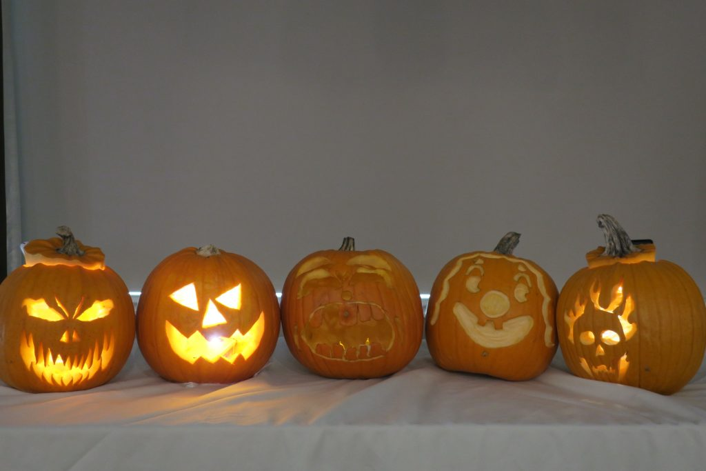 Five jack-o-lanterns with candles inside.