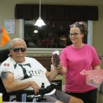 A caregiver in a pink t-shirt hands something to a senior in dark sunglasses and a wheelchair.