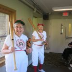 Two seniors in baseball uniforms holding wooden bats and smiling big for the camera!