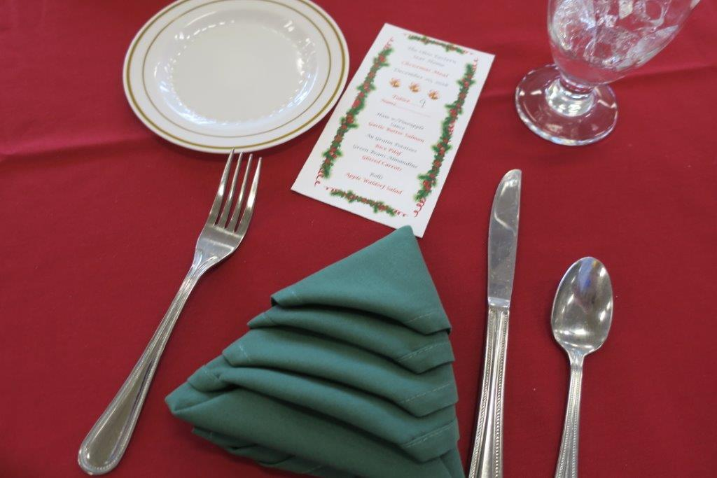 A place set for Christmas dinner with a green napkin folded to look like a Christmas tree.