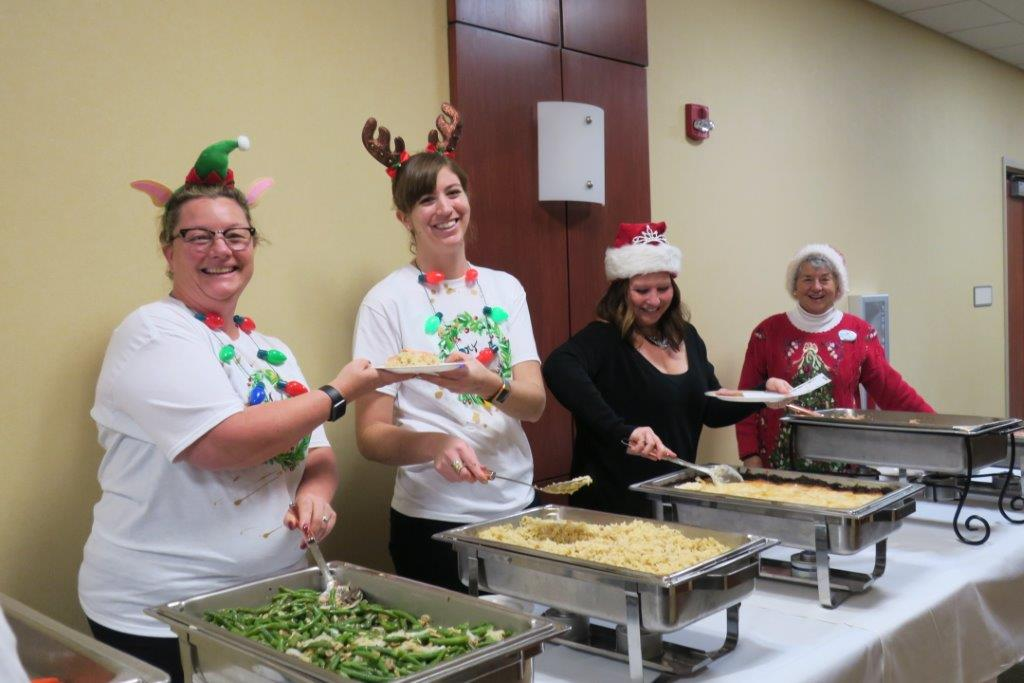 Four smiling ladies serving macaroni and cheese and green beans while dressed up for Christmas.