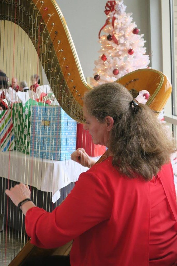 Harpist playing harp in a red dress with a hair clip beside a table filled with gift bags.
