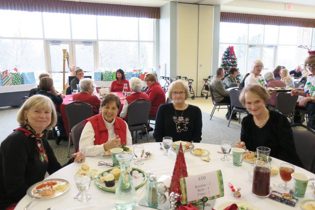 Four smiling women around a Christmas-themed dinner table.