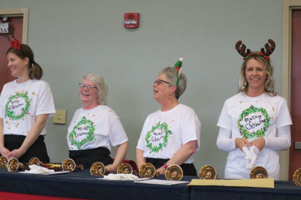 Four women in reindeer antlers play handbells.