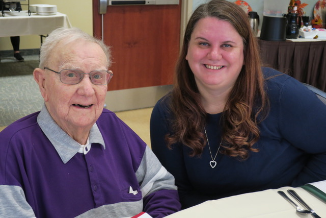 An elderly man in a grey and purple collared button-up beside a smiling redheaded woman in a navy blue long sleeve shirt are at a dining table.