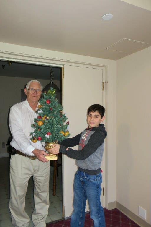 A boy delivers a miniature decorated Christmas tree to an elderly man..