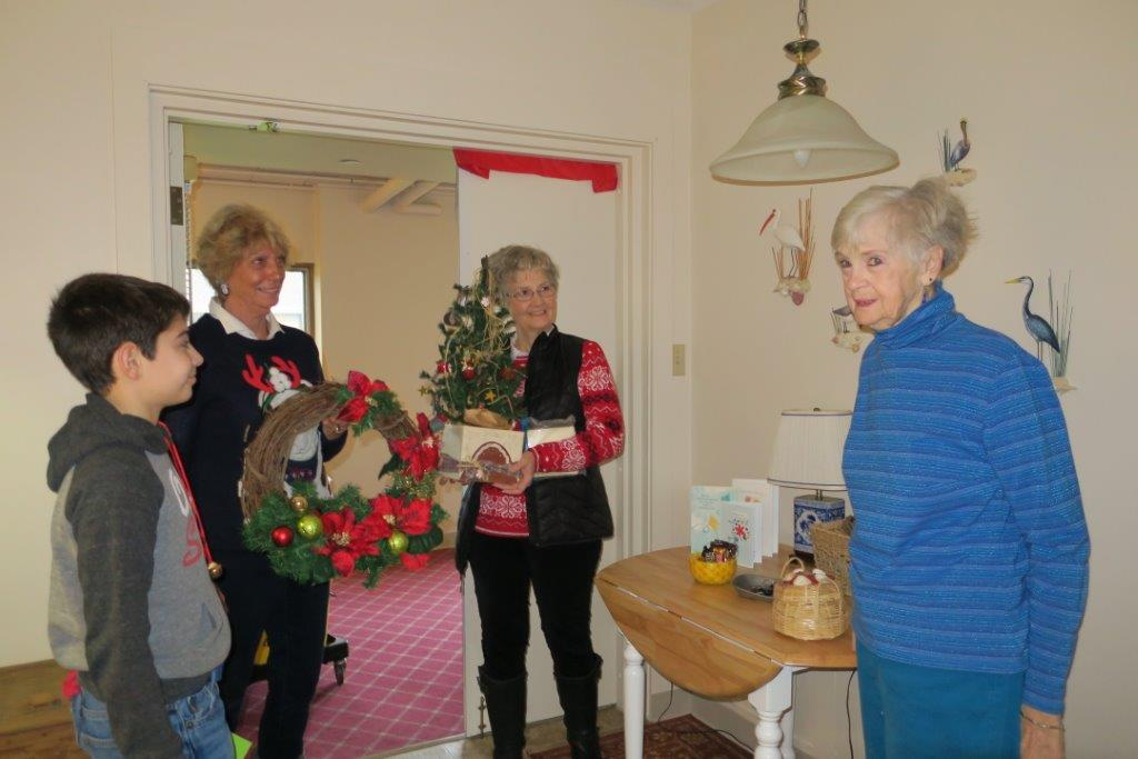 A family of three bring Christmas decorations for their elderly loved one wearing all blue.