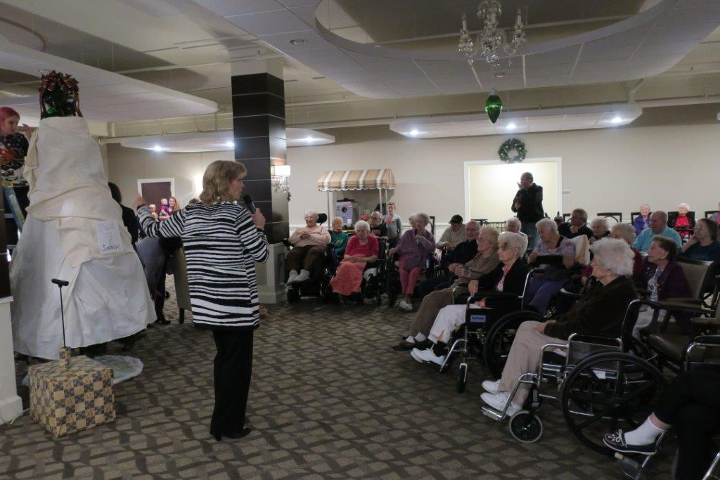 Woman in black and white striped sweater addresses elderly folks with a microphone.