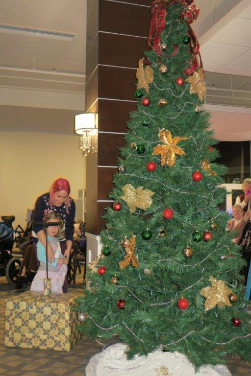 A woman with pinkish red hair holds a little girl back from getting to the presents under a Christmas tree.