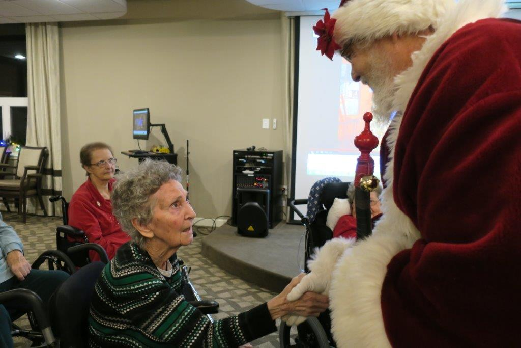 Santa Claus shaking the hand of a woman in a green and black striped sweater.