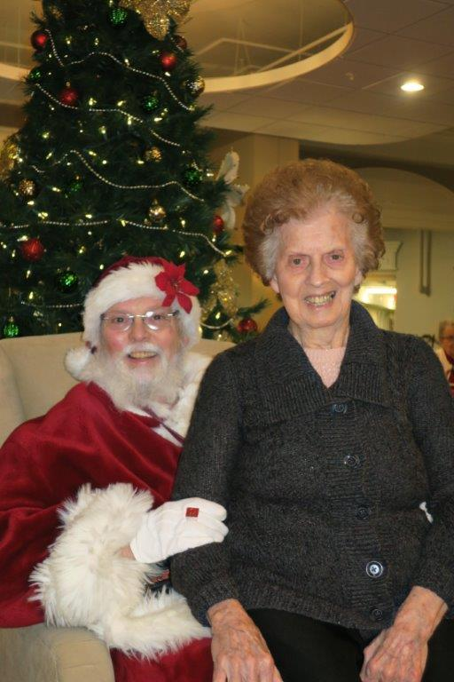 An elderly woman with red and grey hair sitting on Santa Claus' lap in front of a decorated Christmas tree.