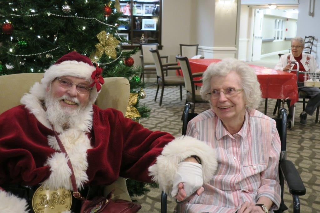 Santa Claus holding the hand of a smiling elderly woman in a striped shirt sitting in her wheelchair.