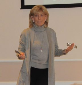 Pretty blonde haired woman in long coat and comfortable grey turtleneck holds a pair of glasses and speaks to a room about OESH.