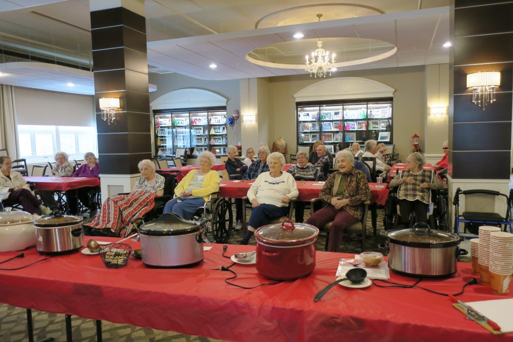 Nursing home residents sitting in front of a table of different chilis in crockpots.
