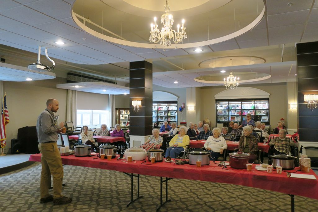 Nursing home residents, a table with crockpots of chili, and a man in corduroy pants and a long sleeve shirt.