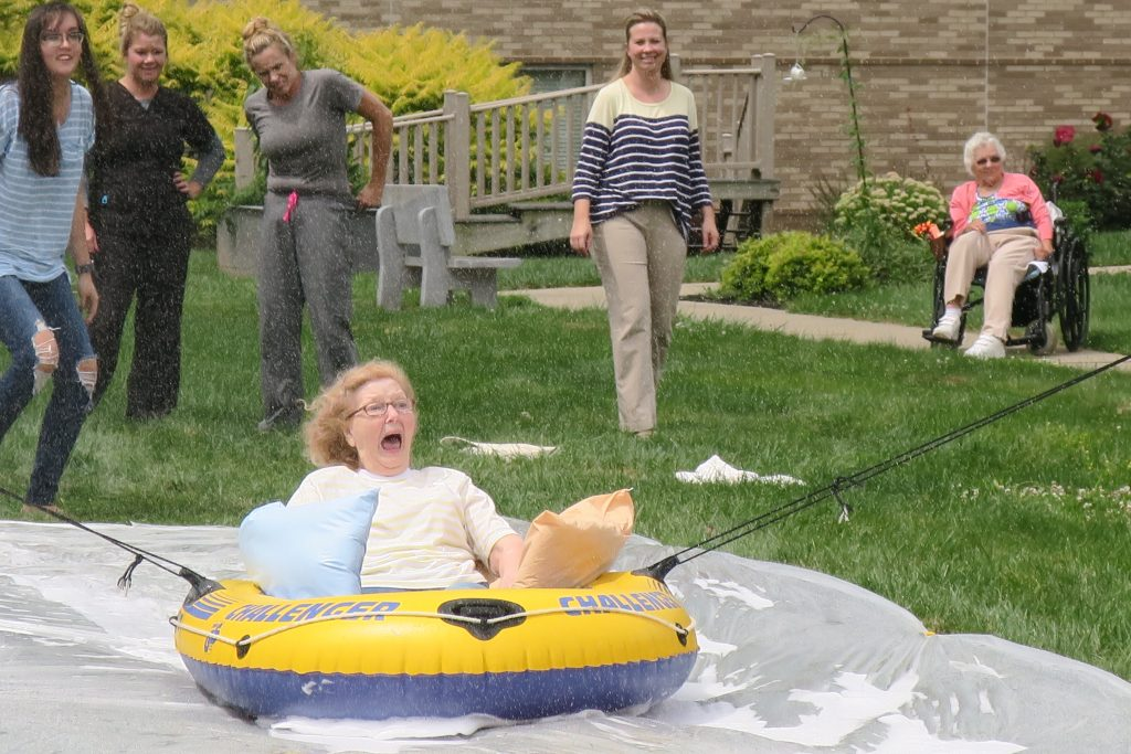 Elderly redhead woman screaming on a slip-n-slide inner tube.