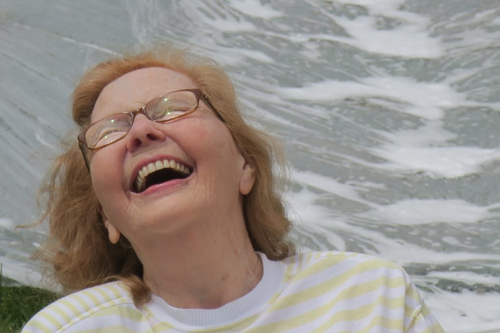 Red-haired woman with glasses throwing her head back in laughter.