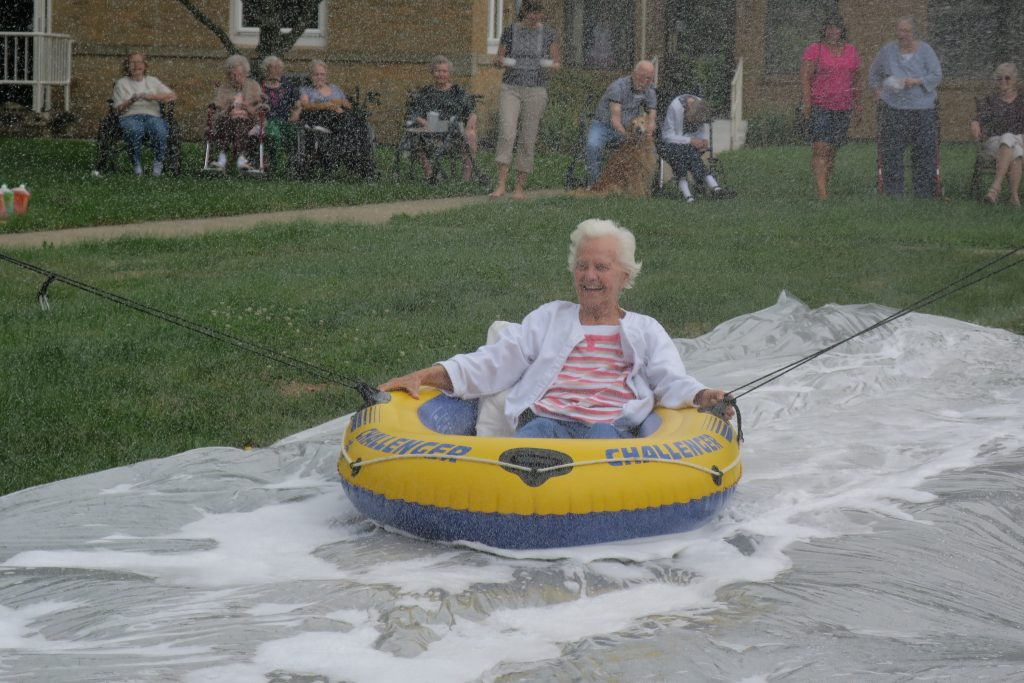 Woman laughing on an inner tube slip-n-slide as folks watch from the grass.