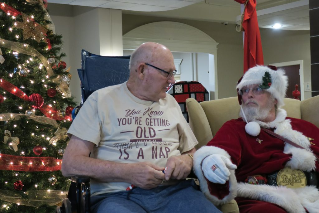 Old man with tan shirt talks to Santa in front of a Christmas tree.