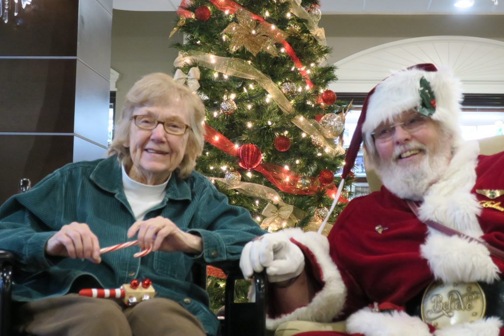 Santa Claus and an elderly woman with a candy cane both light up the room with their smiles.