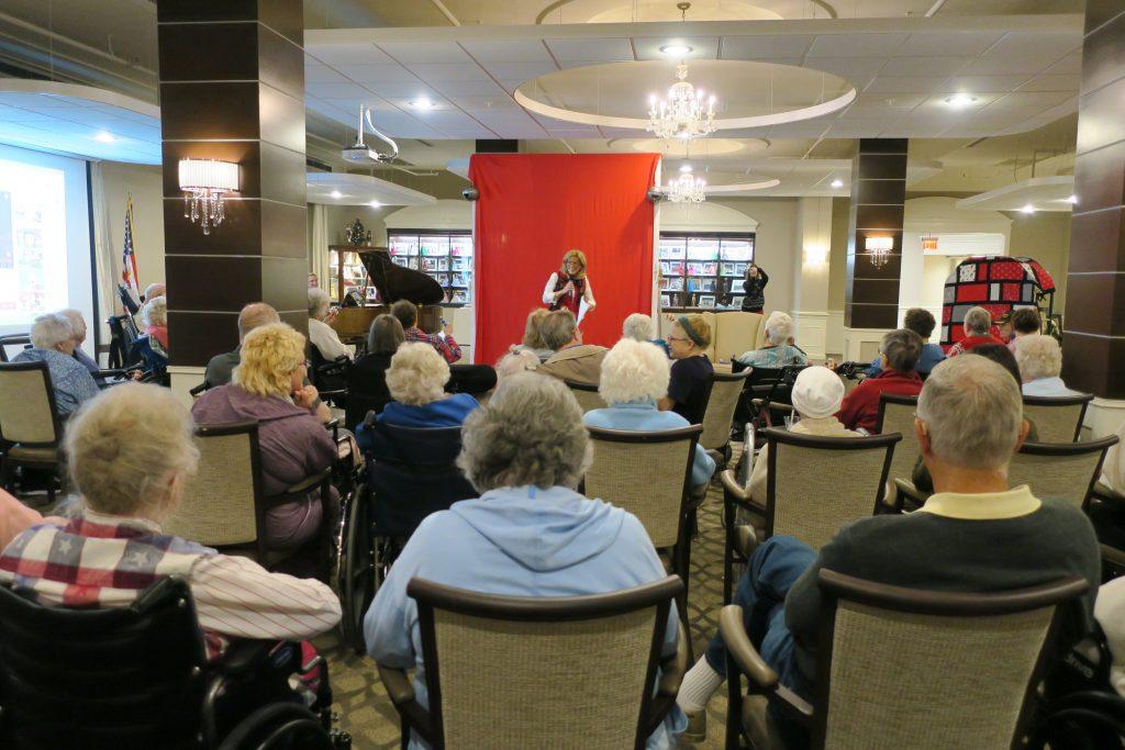 Woman giving a speech at a nursing home.