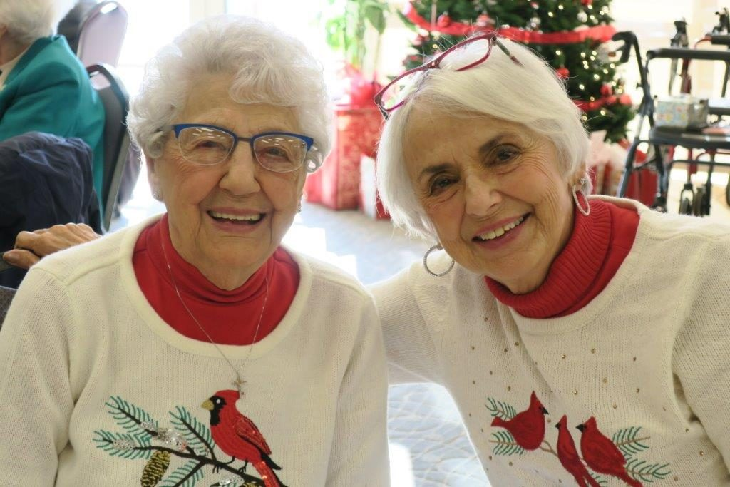 Two smiling, white-haired women in Christmas sweaters.