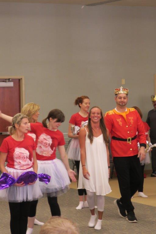 Man in crown dancing with a room of women in tutus.