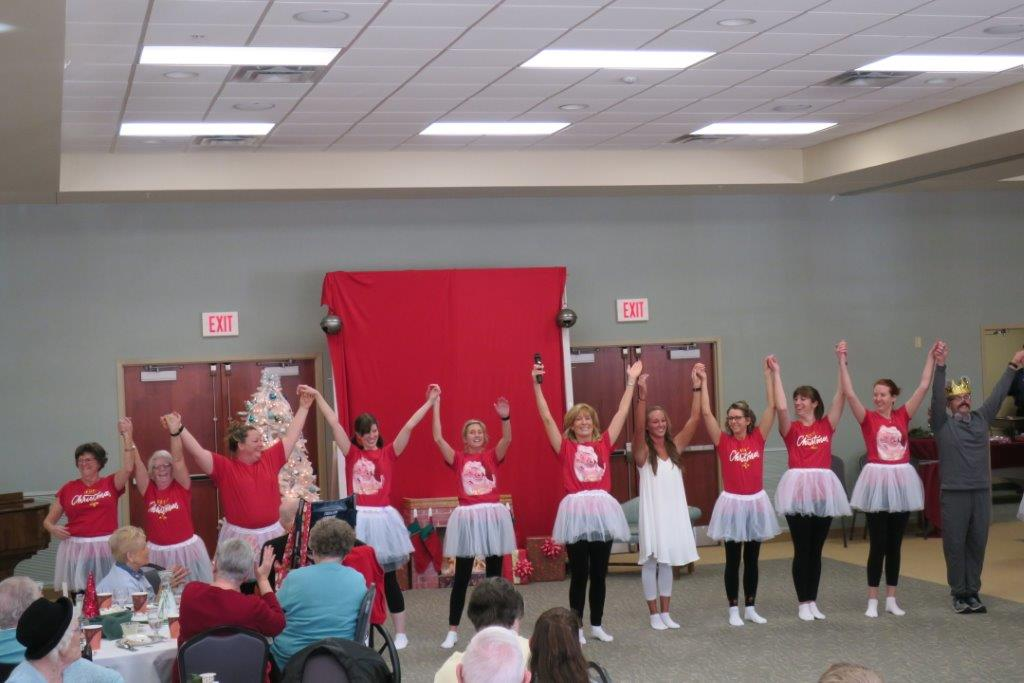 A group of women in red shirts and tutus holding each other's hands up high to an audience.