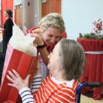 Smiling woman giving a woman in a wheelchair a gift.