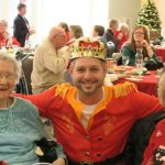 Man in a crown with two grandmotherly women.