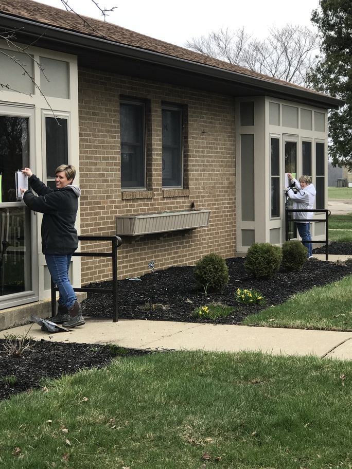 Two women posting COVID-19 notices on doors at the Ohio Eastern Star Home campus.