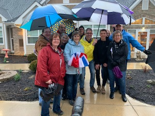 A group of folks with umbrellas and raincoats in the rain.