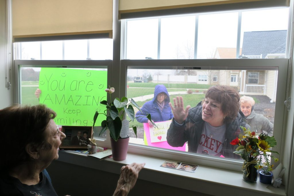 """A couple of women holding a sign that says """"You are amazing"""" and waving through a window at a smiling man to combat senior isolation during COVID."""