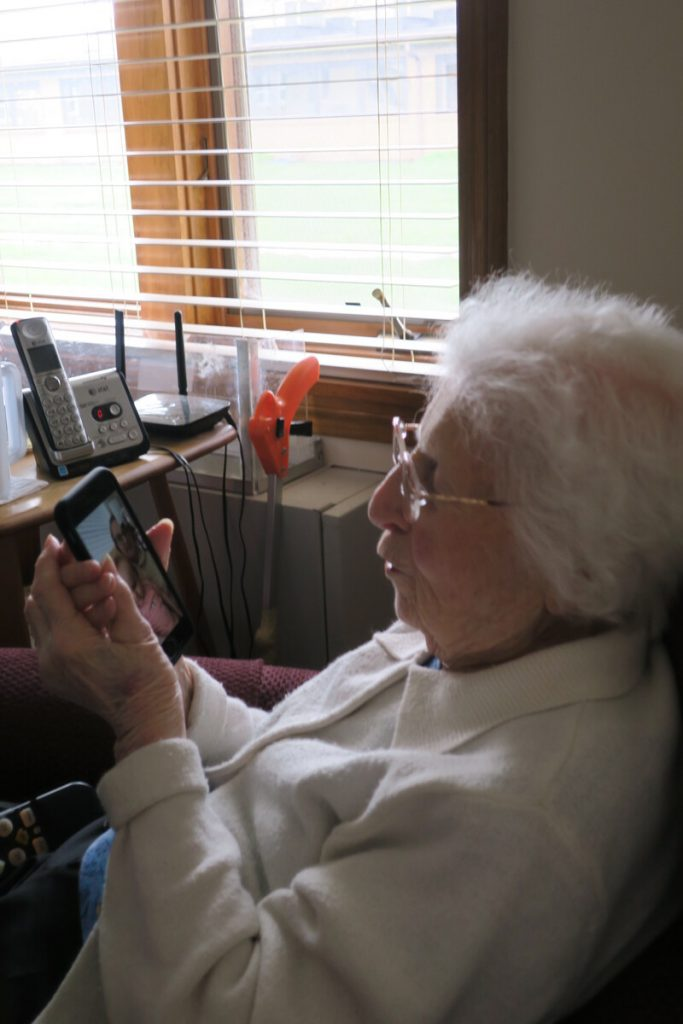 Elderly woman looks at her mobile device.