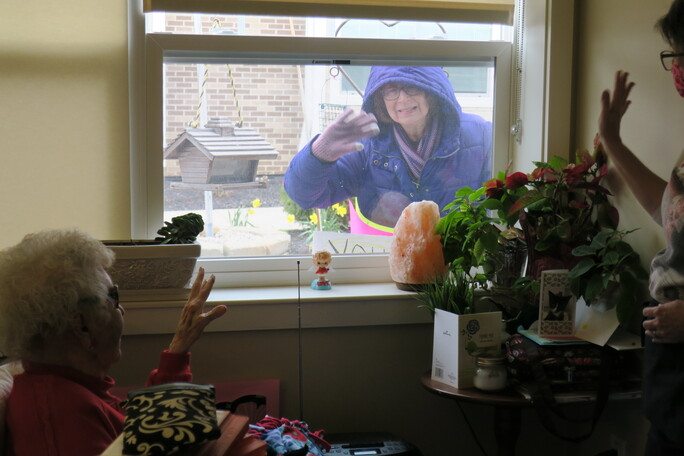Woman in purple winter hoodie waves through window at an elderly woman inside.