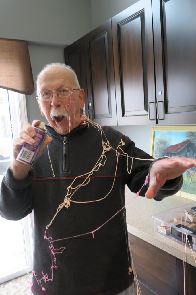 Grandpa holds a can of silly string after spraying himself all over with it.