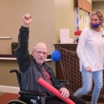 An older man in a wheelchair raises a fist and holds a red pool noodle in his other hand.