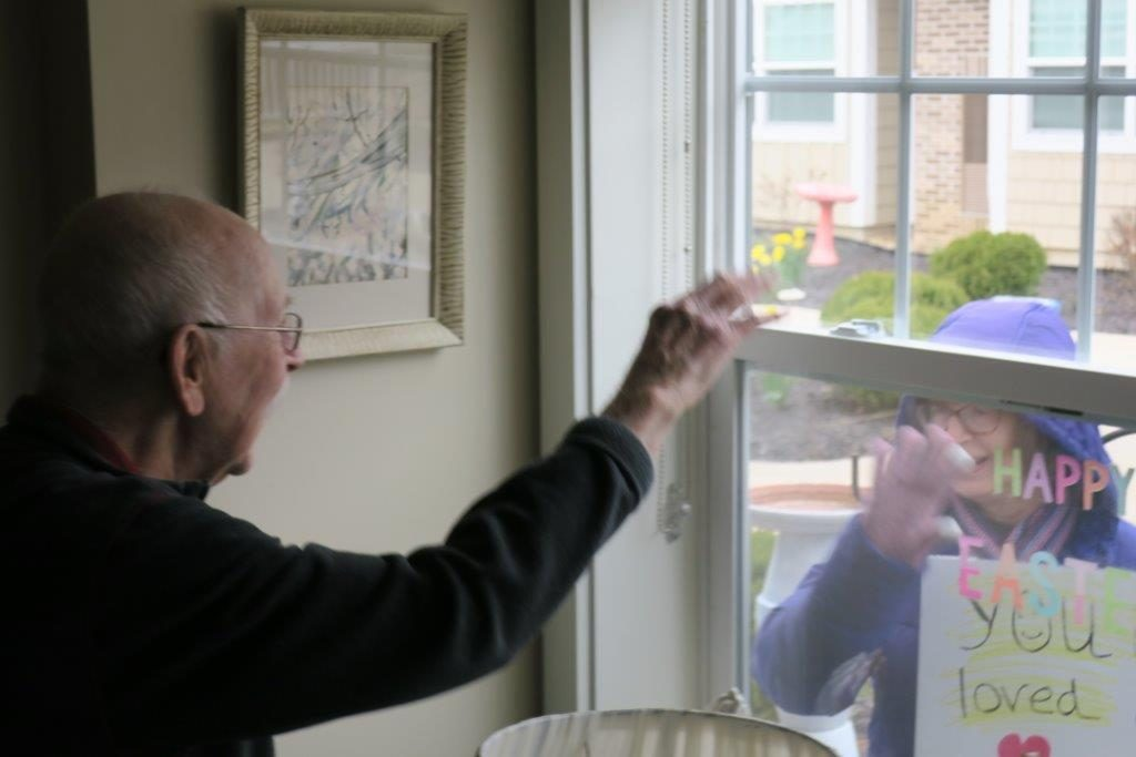 """Woman shows a """"Happy Easter! You are loved"""" sign to an elderly man from outside his window."""