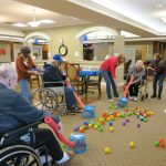 Nursing home residents play a fun and silly game with pool noodles, plastic balls, and laundry baskets while stuck indoors during COVID-19.