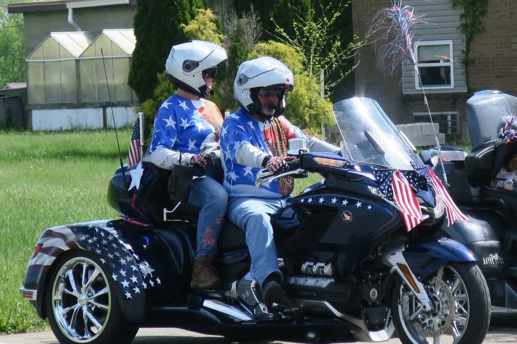 Memorial Day bikers on an American-themed, three-wheeled motorcycle.