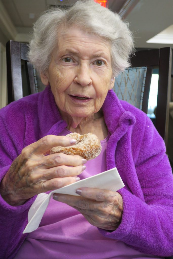 Elderly woman in a lavender coat enjoying a donut.