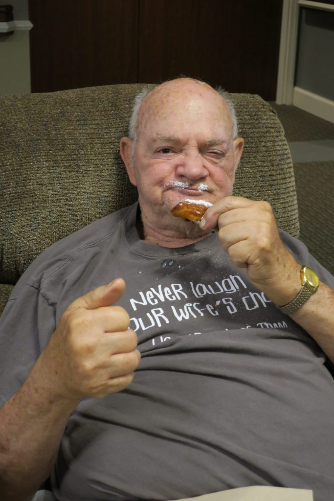 Elderly man eating a powdered doughnut with a gold watch on.