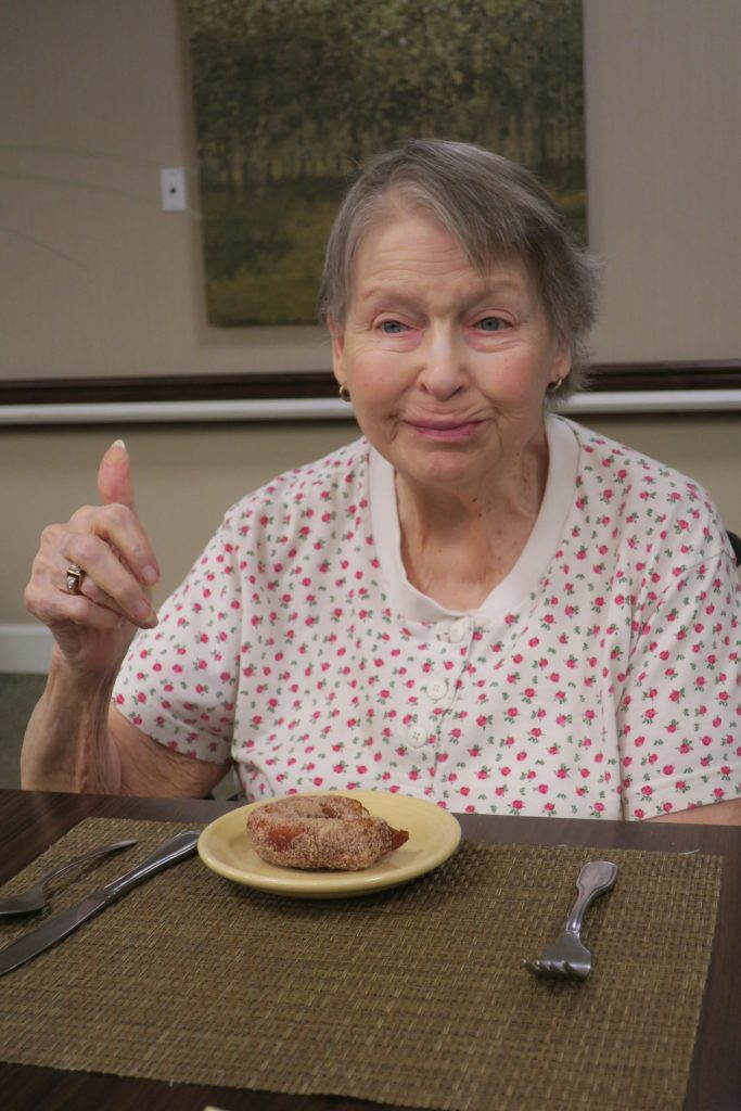 Elderly woman eating a doughnut at the table.