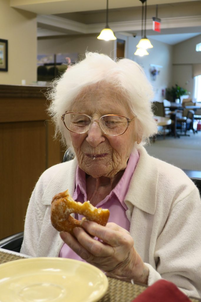 Elderly woman after taking a bite out of a donut.