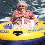 Elderly woman in floral shirt smiling ear to ear on an inner-tube slip-n-slide.