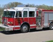 Fireman waving from firetruck driver's seat.