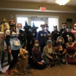 A group of folks in a room all dressed up for Halloween.