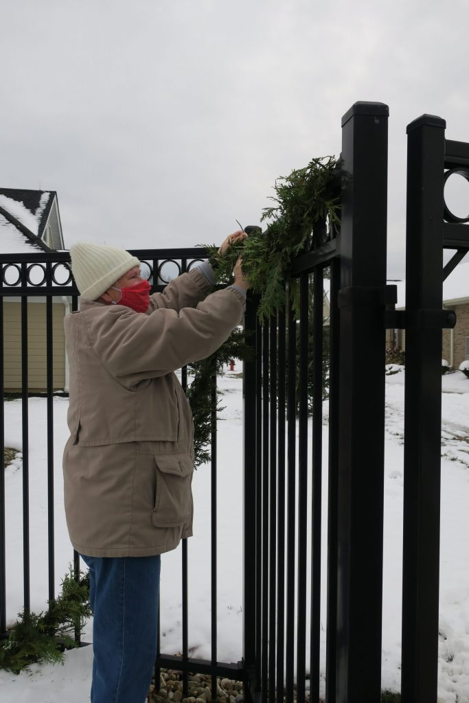 A man in a red mask putting garland up.