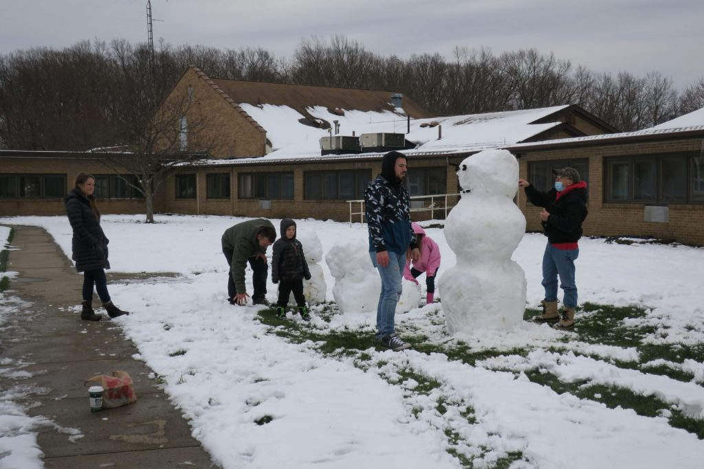 Six people building a snowman.